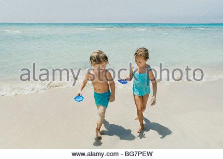 Jungen und Mädchen spielen am Strand - Stockfoto