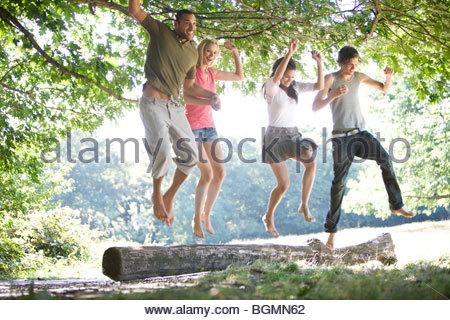 Vier Freunde, die aus einem Stamm springen - Stockfoto