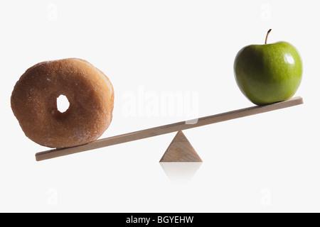 Donut und Apple auf Teeter Totter ausgeglichen - Stockfoto