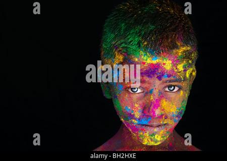 Jungen in farbigen Pulver Pigment vor einem schwarzen Hintergrund abgedeckt. Indien - Stockfoto