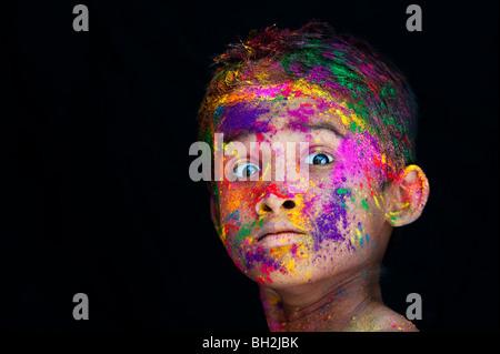 Überrascht Jungen in farbigen Pulver Pigment vor einem schwarzen Hintergrund abgedeckt. Indien - Stockfoto