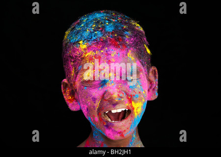 Jungen weinen vor Lachen, während in farbigen Pulver Pigment vor einem schwarzen Hintergrund abgedeckt. Indien - Stockfoto