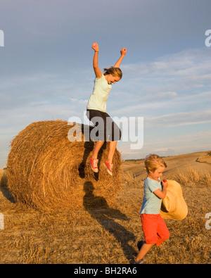 Mädchen und Jungen mit Heuballen - Stockfoto