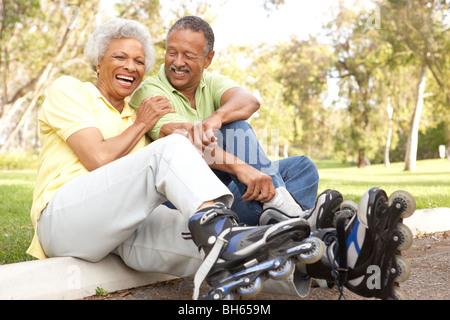 Älteres paar aufsetzen In Line Skates im Park - Stockfoto