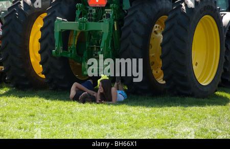 Dieses junge Teen paar erfreuen sich einen ruhigen Moment der Schatten zusammen unter einem Traktorreifen. - Stockfoto
