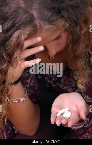 Junge Frau mit Pillen in die hand gedrückt - Stockfoto