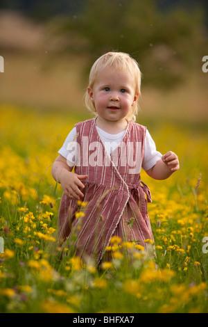 Kleines Mädchen, die zu Fuß in ein Feld von gelben Blüten, Baden-Württemberg, Deutschland - Stockfoto