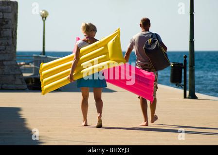 Junges Paar zu Fuß zum Strand mit aufblasbaren Luftmatratzen von rosa und gelb - Stockfoto