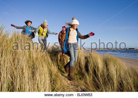 Freunde gehen auf Sanddüne nahe Strand - Stockfoto