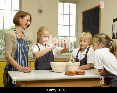 Ein Lehrer kocht mit Kindern - Stockfoto