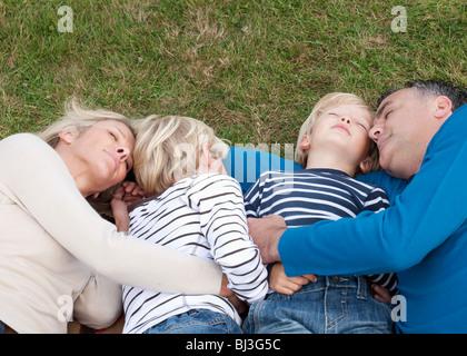 Familie gemeinsam auf dem Rasen liegend - Stockfoto