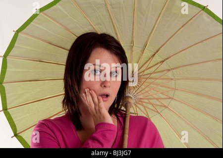 Porträt des schönen Mädchens mit grünen Regenschirm - Stockfoto