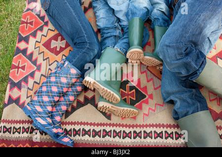 Familie auf Teppich im freien liegend - Stockfoto