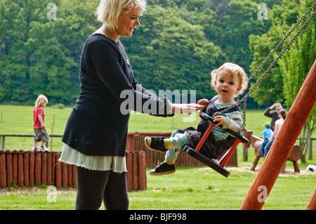 Junge auf einen Tag mit seiner Familie auf einer Schaukel von seiner Mutter gedrängt. - Stockfoto