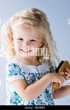 kleines Mädchen, die ihr Haar Bürsten - Stockfoto