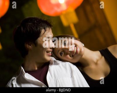 Paar im Freien bei Nacht lächelnd umarmen - Stockfoto