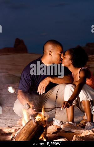 Paar sitzen vor dem Lagerfeuer am Abend - Stockfoto