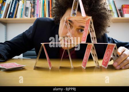 Mann, der eine Pyramide aus Spielkarten - Stockfoto