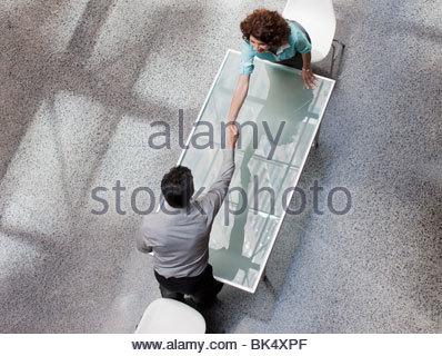 Geschäftsmann und Geschäftsfrau, die Hände zu schütteln, über Tisch erreichen - Stockfoto