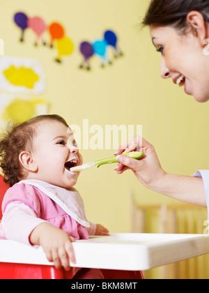 Mutter zu ihrer Tochter am Hochstuhl homogenisierte Nahrung geben. Vertikale Form - Stockfoto