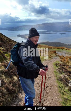 Aktive ältere Menschen gehen Bergwandern in the Trossachs National Park, Schottland - Stockfoto