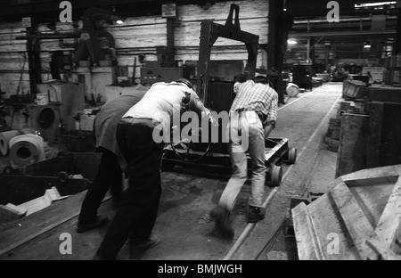 Arbeiter drücken Trolley von geschmolzenem Metall in Black Country Gießerei, West Midlands, England - Stockfoto