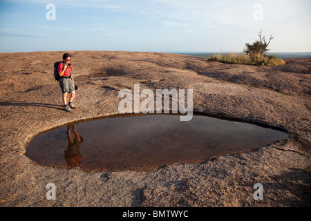 Wanderer am frühlingshaften Pool auf Granit Kuppel Enchanted Rock State Natural Area Texas USA - Stockfoto