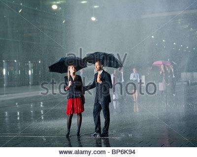 Ein paar steht im Regen unter Sonnenschirmen - Stockfoto
