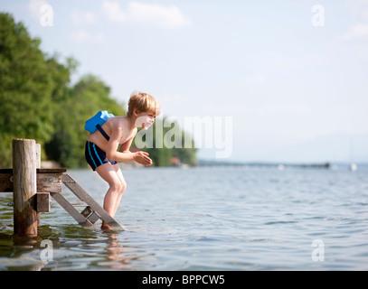 Junge springt in Wasser mit Schwimmen Gürtel - Stockfoto