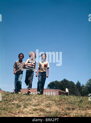 1970 1970S ZWEI AFROAMERIKANISCHE EINEN WEIßEN JUNGEN ZU FUß ÜBER GRASS - Stockfoto