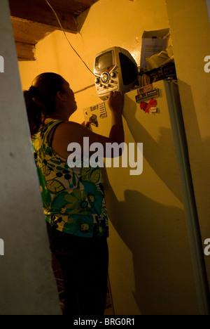 Guadalupe Ordinola spielt und singt zusammen mit ihrer Karaokemaschine in der kleinen Küche von ihrer Familie Haus. - Stockfoto