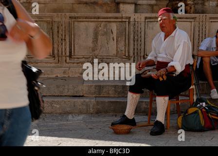 Ein Alter Mann in Tracht, die Mandoline zu spielen, im Schatten der großen Onofrio Brunnen. Placa, Dubrovnik, Dalmatien, - Stockfoto