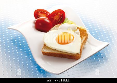 Toast mit herzförmigen Spiegelei und Tomaten - Stockfoto