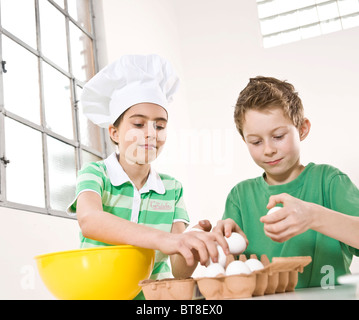 Mädchen tragen eine Kochmütze und ein Junge cracking Eiern in eine Schüssel geben - Stockfoto
