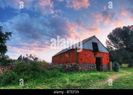 Niedrigen Winkel Blick auf eine alte Scheune und ein bewölkter Himmel - Stockfoto