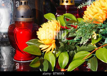 Rote Kerzen und künstliche Blumen auf ein Grab - Stockfoto