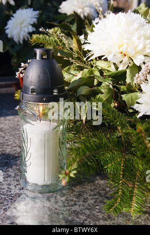Weiße Kerze und künstliche Blumen auf ein Grab - Stockfoto