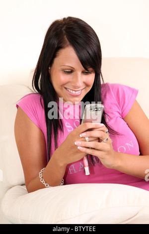 Junge glückliche Frau sitzt alleine auf dem Sofa Lesen einer Nachricht auf ihr Handy - Stockfoto