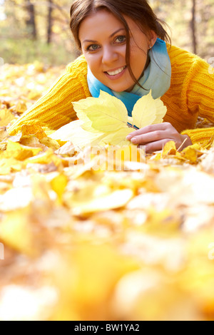 Foto von ruhenden junge Frau liegend auf Laub im Herbst - Stockfoto
