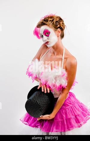20 - 30 Jahre alt, weiblich in rosa, gefiederten Outfit und bemaltem Gesicht hält einen schwarzen Hut.  Dieses Bild - Stockfoto