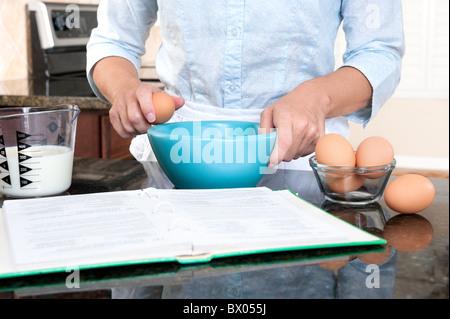 Eine Hausfrau Risse während der Anweisungen von einem Kochbuch ein Ei in eine Rührschüssel geben. - Stockfoto