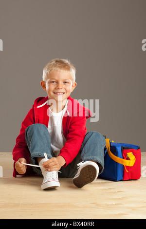 Ein Junge, einen Bogen mit einem Schnürsenkel binden - Stockfoto