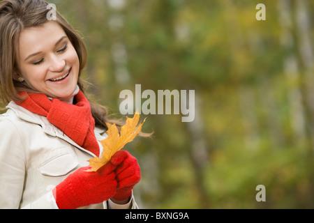 Bild des jungen Mädchens in warme Kleidung hält orange Blatt im Herbst - Stockfoto