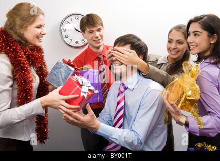 Foto von fröhlichen Geschäftsfrau, halten sie die Hände auf den Augen des Mannes während ihrer Kollegen bereitet - Stockfoto