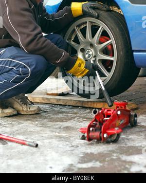 Ein Mechaniker die Radmuttern mit einem Schraubenschlüssel abschrauben, das Rad von einem Auto, Rigger Handschuhe - Stockfoto