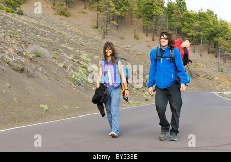 El Hierro, Kanarische Inseln, Spanien. Junges Paar Rucksacktouristen Wandern auf Weg durch einen Kiefernwald in - Stockfoto