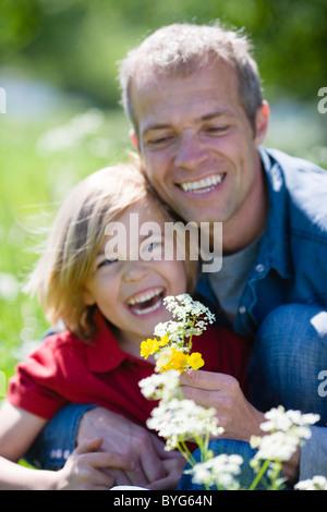 Vater und Sohn mit Blüten in hellem Sonnenlicht - Stockfoto