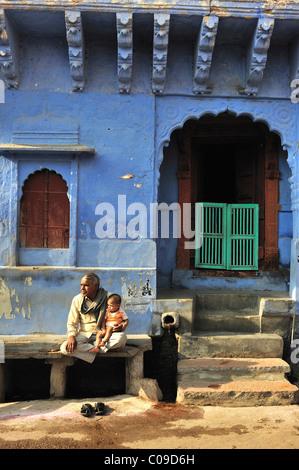Älterer Mann mit einem Kind auf Steinbank vor seinem Haus, Jodhpur, Rajasthan, Indien, Asien - Stockfoto