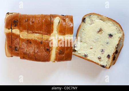 Warburtons Hot Cross Bun Brot Brot mit einer Scheibe bereit für Ostern gebutterte auf weißem Hintergrund - Stockfoto