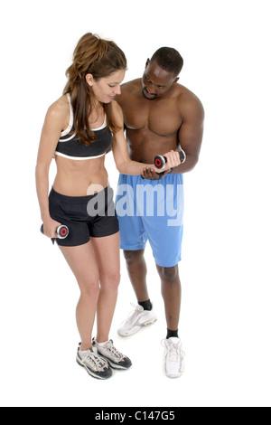 Frau im Fitness Training Kleidung bekommt Hilfe von einem männlichen personal Trainer im Umgang mit Hanteln. Isolierte - Stockfoto